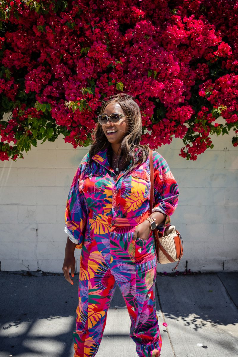 Krewe SONIAT Sunglasses, Farm Rio Jumpsuit. | Summer Jumpsuit by popular LA fashion blogger, Alicia Tenise: image of a woman wearing a summer jumpsuit with a pair of white sneakers and standing under a pink floral plant.