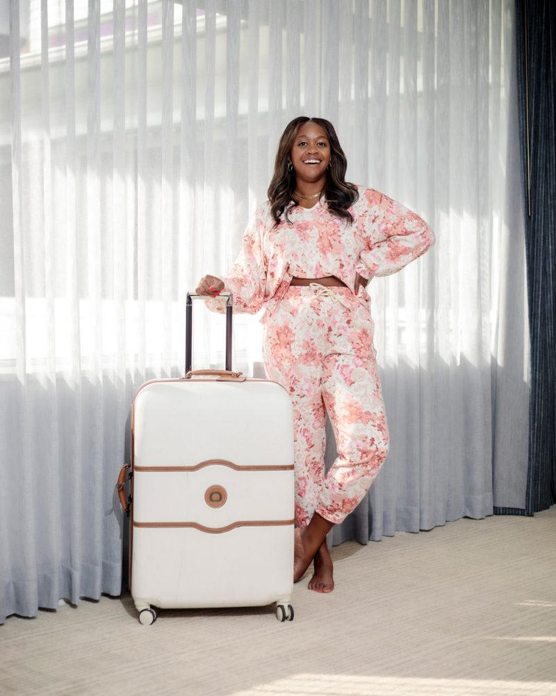 What to Wear on a Road Trip by popular LA fashion blogger, Alicia Tenise: image of Alicia Tenise wearing pink and white floral print pajamas and standing next to a white rolling suitcase.