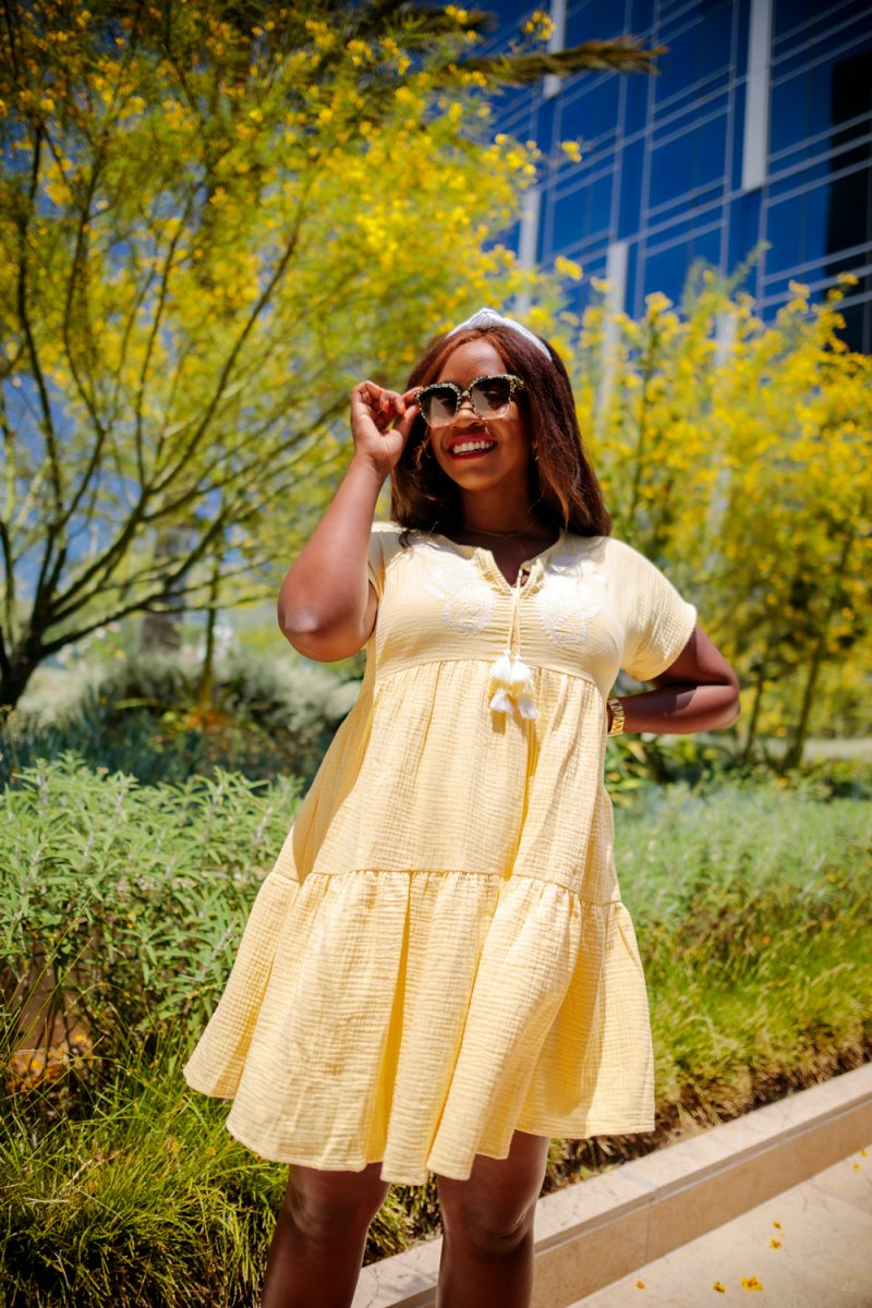 Scoop Women's Short Sleeve A-Line Short Dress with Tassels | Summer Essentials From Walmart by popular LA fashion blogger, Alicia Tenise: image of a woman standing outside and wearing a Scoop short sleeve a-line yellow dress with a knotted headband and gladiator sandals.