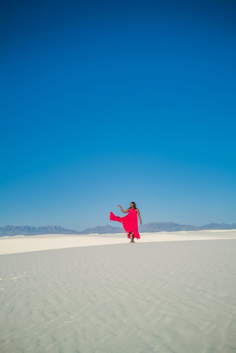 White Sands National Park   Blogging Tips by popular LA lifestyle blogger, Alicia Tenise: image of Alicia Tennis wearing a flowing pink maxi dress and walking barefoot at White Sands National Park.