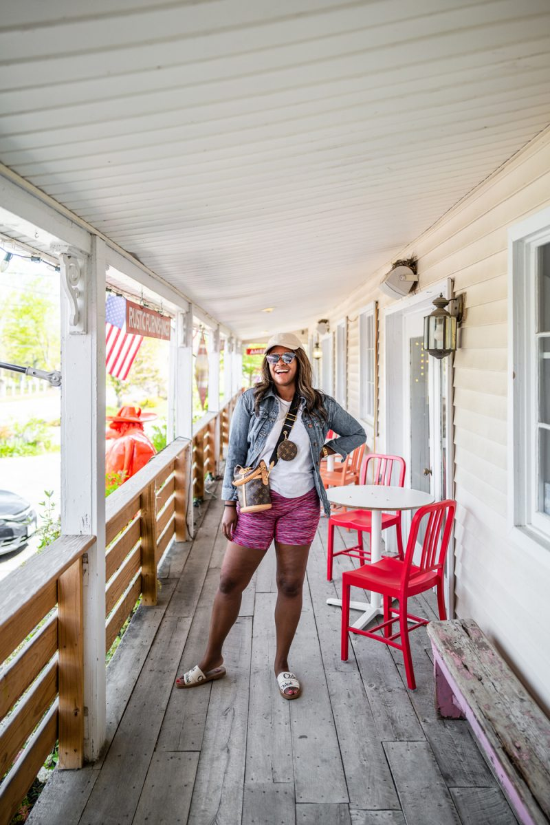 What to Wear on a Road Trip by popular LA fashion blogger, Alicia Tenise: image of Alicia Tenise wearing pink biker shorts, white t-shirt, white slide sandals, tan baseball hat, and denim jacket.