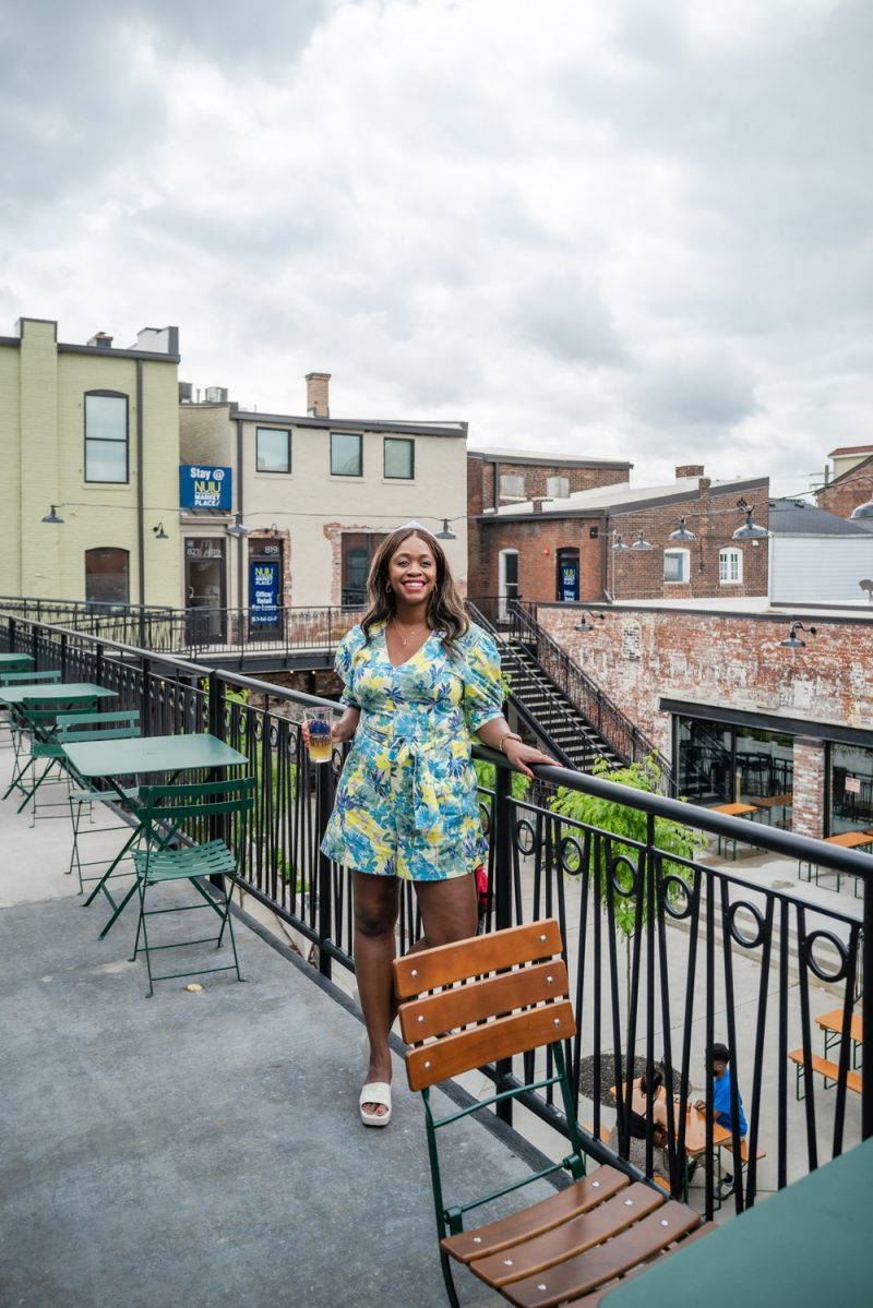Louisville Kentucky, Nulu Marketplace, Tanya Taylor Becky Romper   Louisville KY Road Trip by popular LA travel blogger, Alicia Tenise: image of Alicia Tenise standing on a balcony and wearing a Tanya Taylor Becky Romper.