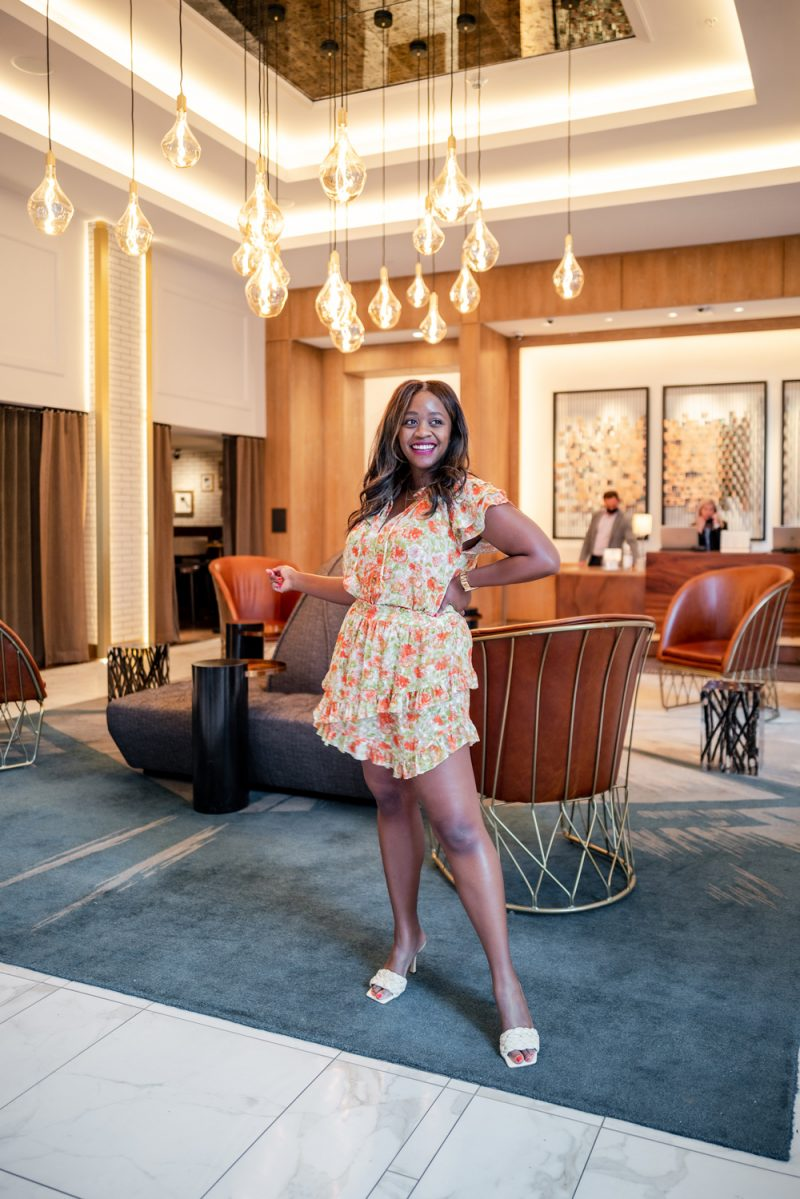 Misa Los Angeles Floral Maria Top and Floral Palma Skirt    Louisville KY Road Trip by popular LA travel blogger, Alicia Tenise: image of Alicia Tenise standing in a lobby and wearing floral top and matching floral shorts.