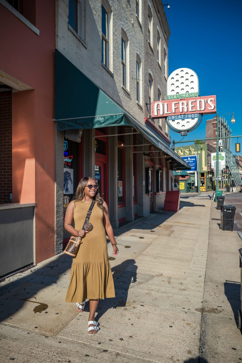 What to Wear on a Road Trip by popular LA fashion blogger, Alicia Tenise: image of Alicia Tenise wearing a brown sleeveless maxi dress and walking outside on sidewalk by Alfred's.