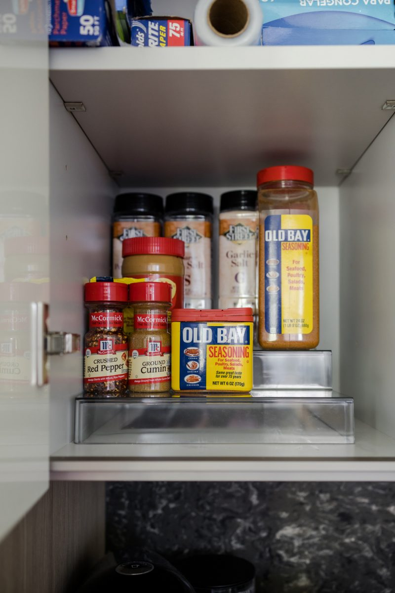 How to Organize a Small Kitchen by popular LA lifestyle blogger, Alicia Tenise: image of a cabinet filled with tin foil, wax paper, and spices.