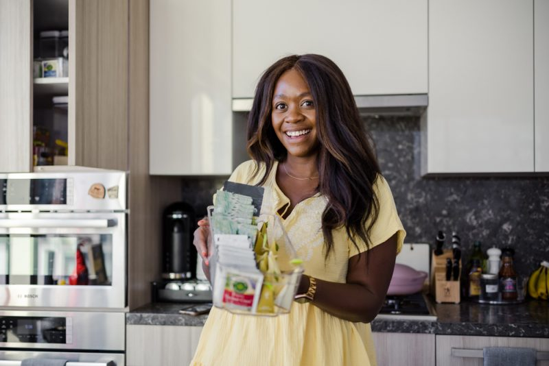 Scoop Women's Short Sleeve A-Line Short Dress with Tassels | How to Organize a Small Kitchen by popular LA lifestyle blogger, Alicia Tenise: image of Alicia Tenise wearing a yellow dress and holding an acrylic bin filled with tea bag.