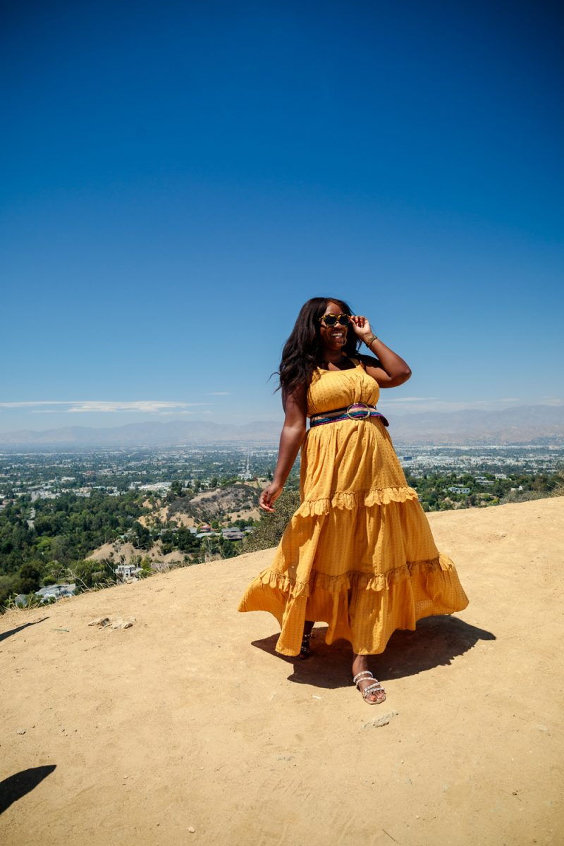 Sezane Albana Dress, Mullholland Scenic Overlook at Coldwater Canyon Park | Colorful Dresses by popular LA fashion blogger, Alicia Tenise: image of Alicia Tenise standing at a overlook and wearing a mustard yellow Swiss dot maxi dress with a pink, blue, and purple stripe waist belt with studded strap sandals and a pair of sunglasses.