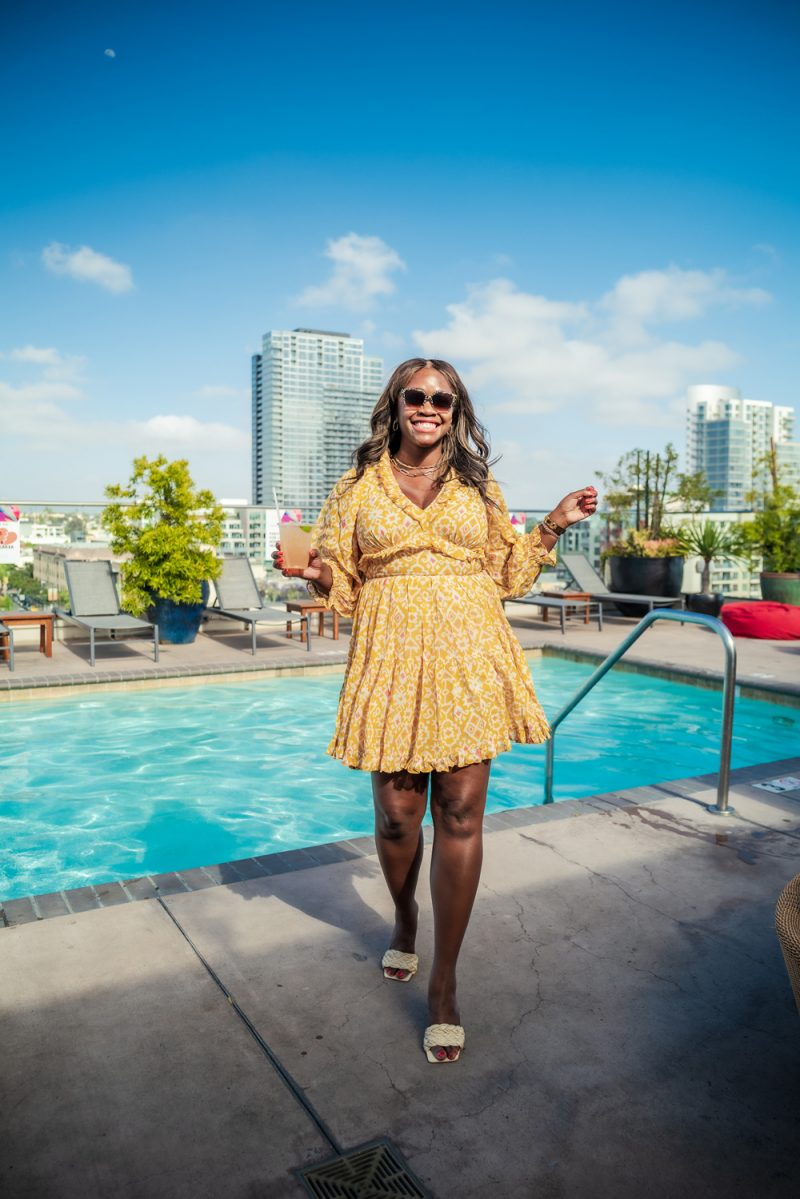 Packing List by popular LA travel blogger, Alicia Tenise: image of Alicia Tenise wearing a yellow long sleeve mini dress and white braided strap sandals while holding a cocktail drink and standing by the pool.