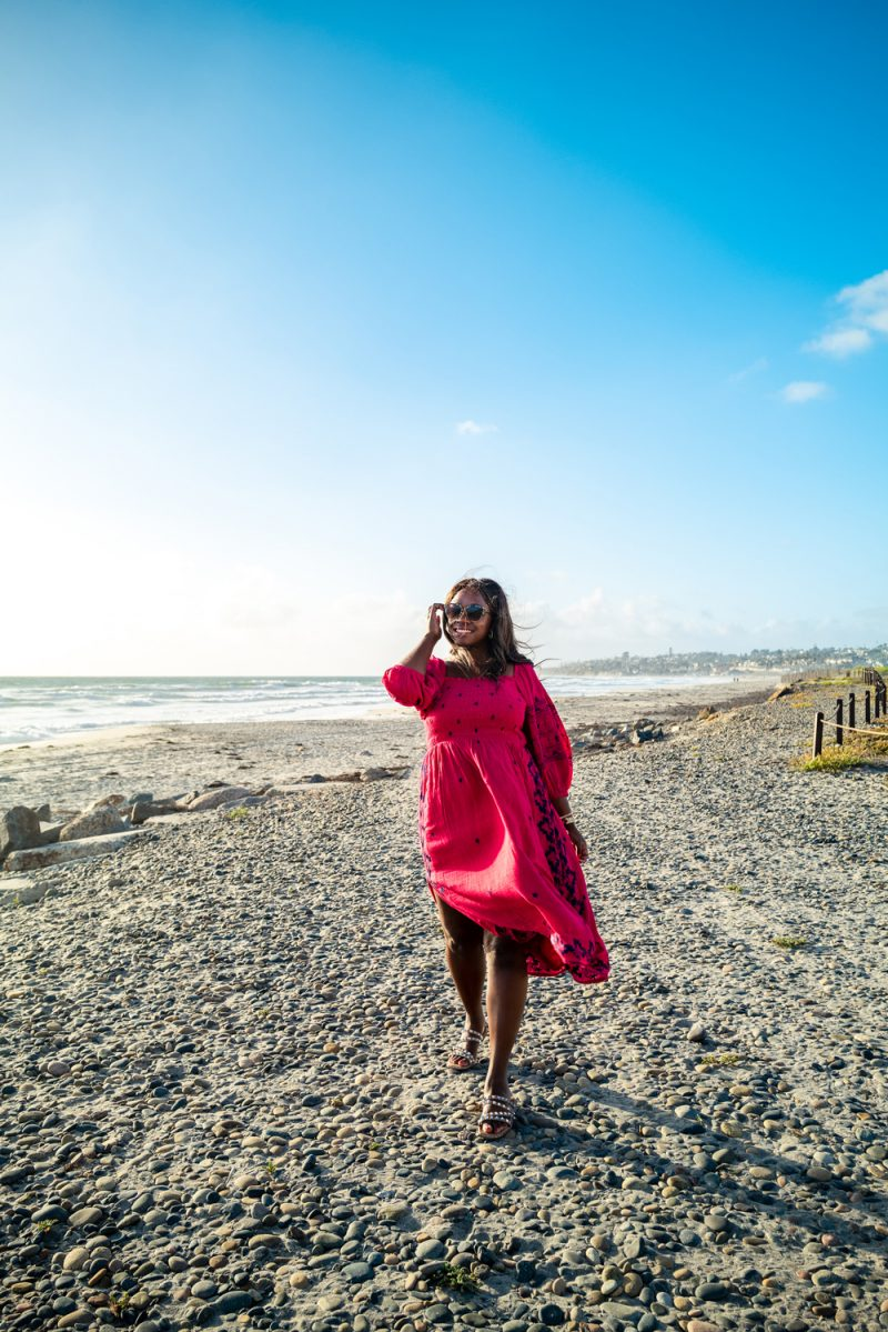 Cardiff State Beach   Packing List by popular LA travel blogger, Alicia Tenise: image of Alicia Tenise standing on a beach and wearing a pink embroidered dress.