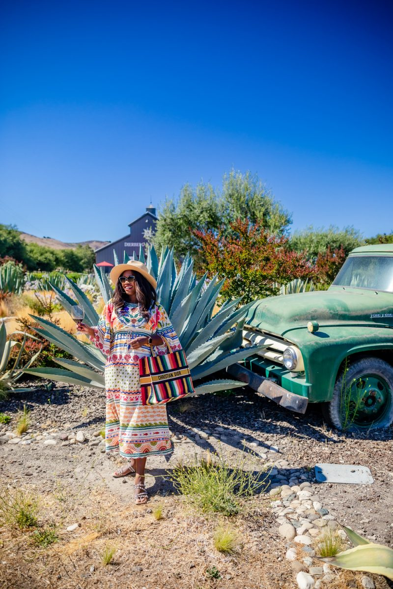 Farm Rio Salt Island Drawstring Midi Dress | Colorful Dresses by popular LA fashion blogger, Alicia Tenise: image of Alicia Tenise standing next to a Agave plant and vintage green pickup truck and wearing a Farm Rio Dres, and straw fedora hat while holding a rainbow stripe Christian Dior bag.