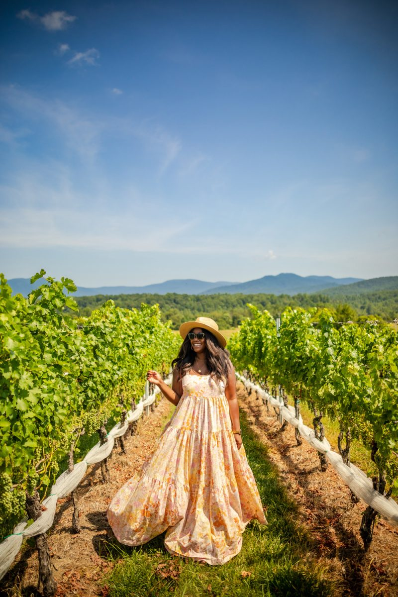 Free People Park Slope Dress | Colorful Dresses by popular LA fashion blogger, Alicia Tenise: image of Alicia Tenise wearing. floral print maxi dress and straw fedora hat while walking through a vineyard.